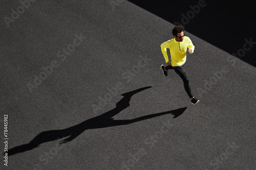 Fotografie, Obraz  Running man sprinting for success on run. Top view athlete runne