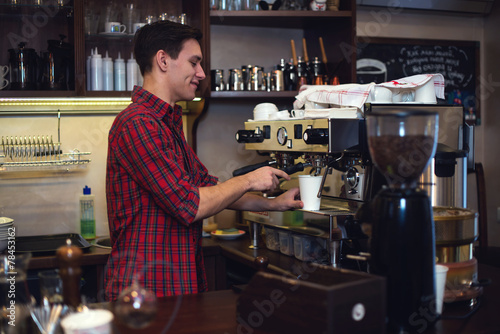 Fotografie, Obraz  Young handsome barista hipster making coffee for his clients in