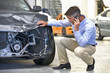 Insurance assessor or driver on mobile phone and inspecting damaged vehicle