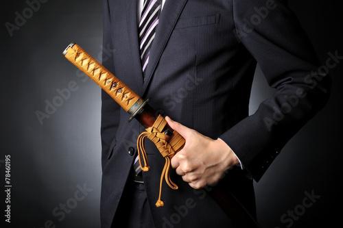 Foto  侍の刀を持っているスーツのビジネスマン