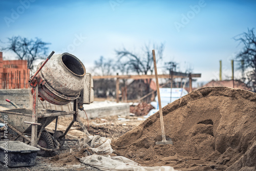 Photo  Cement mixer machine at construction site, tools and sand
