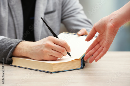 Author signing autograph in own book at wooden table Canvas Print
