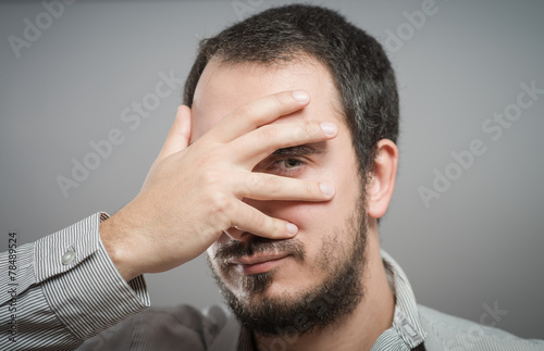 Fotografie, Obraz  Portrait of a handsome man covering his eyes with hand