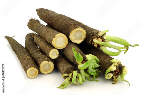 black salsify and some cut ones on a white background