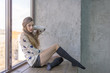Beautiful girl sitting at a window in a warm sweater and socks