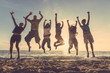 canvas print picture - Multiracial group of people jumping at beach