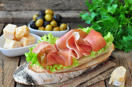 Closeup of delicious parma ham sandwich on wooden backgraund