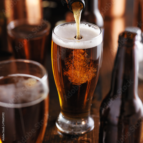 Photo  pourng beer from bottle into glass at bar