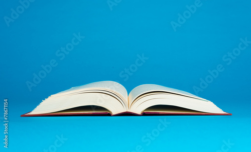 Fotografering  Open book on a blue background