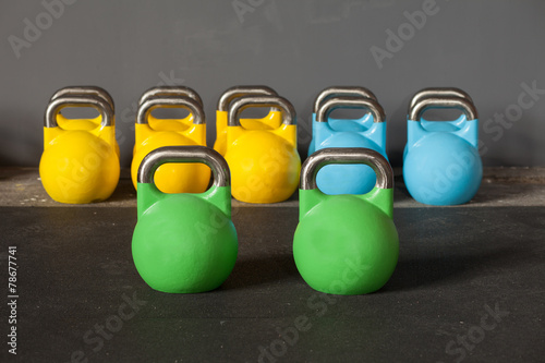 Fototapeta colorful kettlebells in a row in a gym - focus on the front kett