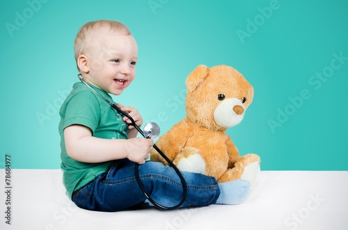Child is a doctor. Playing with teddy bear #78684977