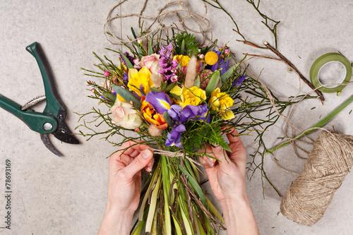 Spoed Foto op Canvas Iris hands of florist making bouquet spring flowers