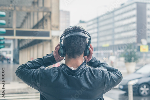 Photo  Back view of a young man with headphones posing in the city stre