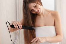 Woman Straightening Hair With ...