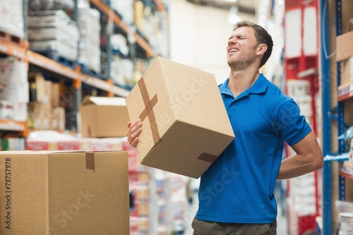 Worker with backache while lifting box in warehouse Wallpaper Mural