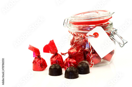 Fotografia, Obraz  a glass jar full of delicious bonbons wrapped in shiny red paper