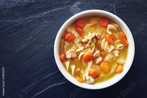 Fotografie, Obraz  top down photo of chicken noodle soup with copy space on slate