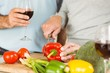 Mature couple having red wine while making dinner