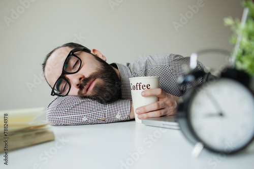 Obraz Man sleeps in office on table over laptop with coffee in hand - fototapety do salonu