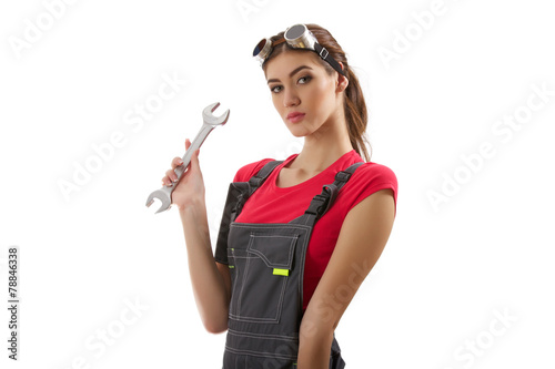 The girl stands with a wrench