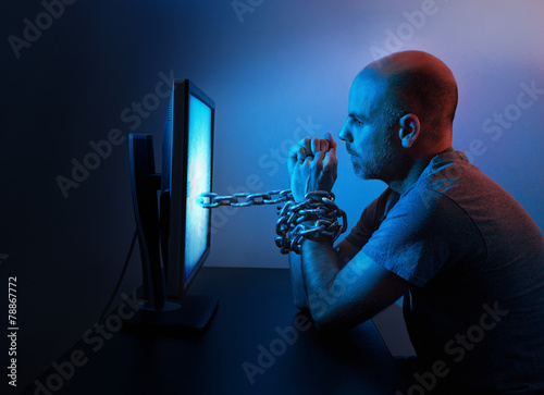 Photo  Man chained to computer