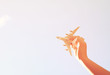 close up photo of woman's hand holding toy airplane against blue