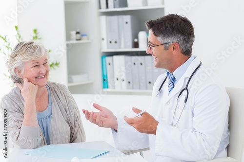 Carta da parati Doctor discussing with senior patient at table
