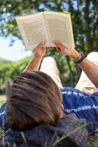 Deurstickers Handsome hipster reading book in park