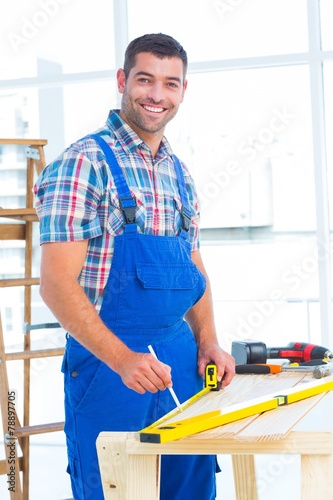Fotografie, Obraz  Smiling handyman using tape measure at workbench in office
