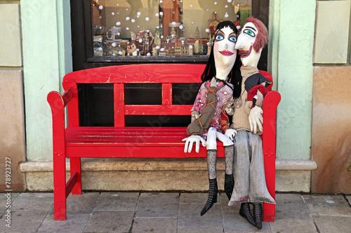 handmade lover dolls on red bench, Bratislava Poster