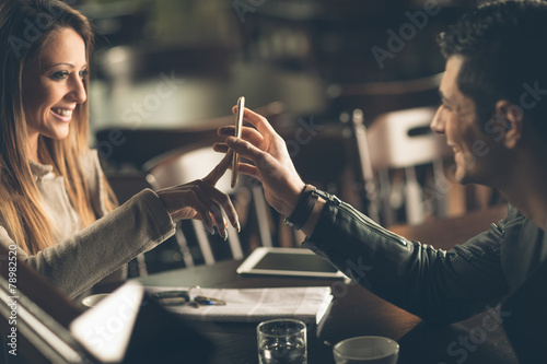 Photo  Fashionable couple at the bar using a smart phone