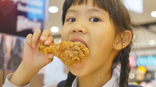 Asian child enjoys eating fried chicken
