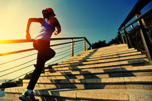 Young Fitness Woman Running On Seaside Stone Stairs