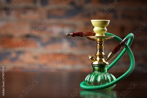 Fotografia  Eastern green hookah on wood table