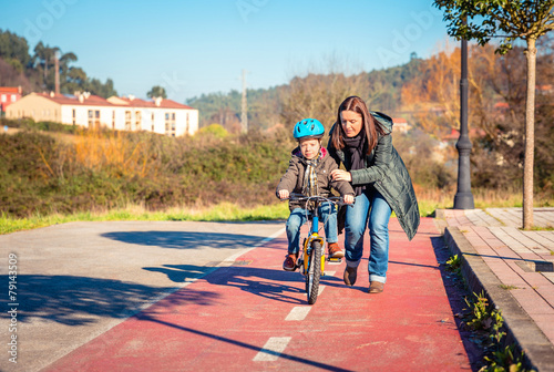 Fotografia, Obraz  Mother teaching son to ride a bike in cycleway