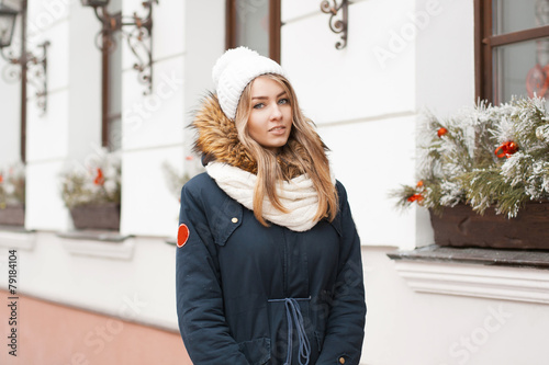 Photo  Beautiful girl in a knitted hat and jacket standing near the wal