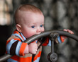 Infant Boy Blue Eyes Biting Wrought Iron Headboard