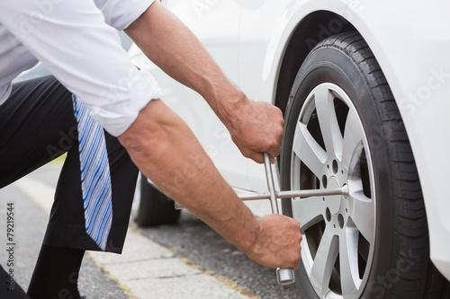 Fotografie, Obraz  Businessman fixing tire