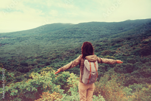 Traveler girl standing with raised arms on mountain