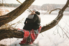 Hipster Couple Sitting On Tree Over Frozen Lake