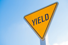 A Yellow Yield Sign Against A Blue Sky Background