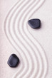 Zen garden with a wave lines in the sand with relaxing black sto