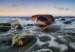zachód słońca nad kamienistą plażą