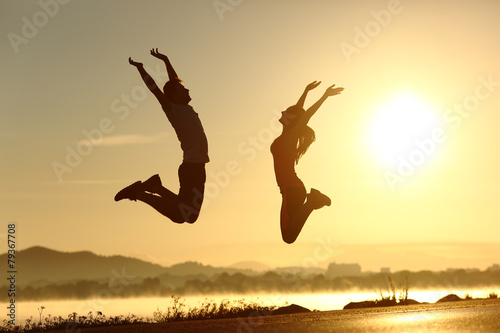 Fitness couple jumping happy at sunset Plakat