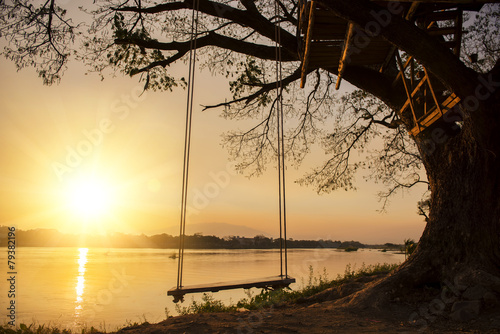 samotna huśtawka po stronie rzeki i zachód słońca, Tajlandia