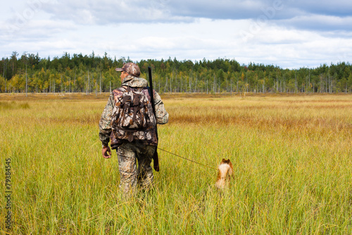 Fotobehang Jacht hunter with a dog crosses the swamp
