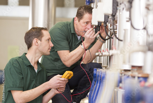 Two male technician repairing agriculture machinery..