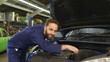 Portrait of a friendly mechanic repairing a car in a garage.