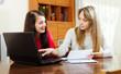 Women looking financial documents in laptop