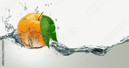 Foto  Orange with green leaves on a background of splashing water.